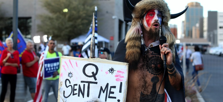A Qanon believer speaks to a crowd of President Donald Trump supporters outside of the Maricopa County Recorder's Office where votes in the general election are being counted, in Phoenix, on Nov. 5, 2020.