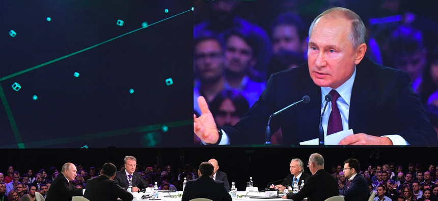 Russian President Vladimir Putin, left, attends a panel discussion at the Artificial Intelligence Journey forum in Moscow on Nov. 9, 2019.