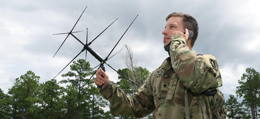A student in the Special Forces Communications Sergeant course uses an AV-2125 satellite antenna with an AN/PRC-117G satellite radio during training.