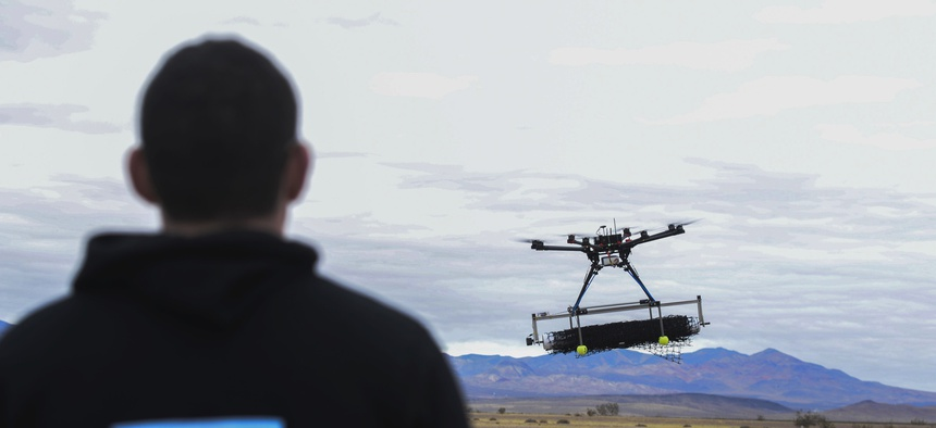 U.S. Air Force 2nd Lt. David Feibus flies one of his team's DJI S1000 drone during the setup and calibration phase of the AFRL Commander's Challenge near Las Vegas in 2016.