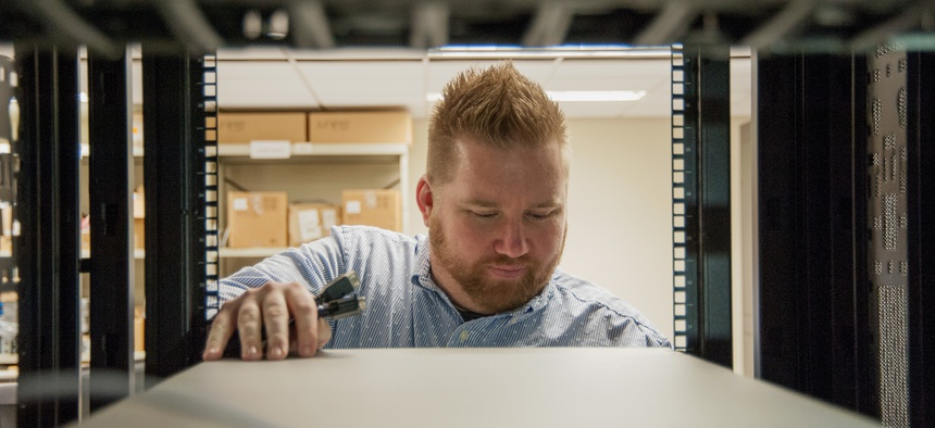 Brandon Simpkins, lead network engineer at Space and Naval Warfare Systems Center Atlantic, examines server operations. Simpkins completed a fellowship at Amazon Web Services.