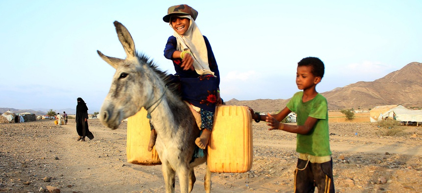 A girl rides a donkey carrying jerry cans filled with water from a cistern at a make-shift camp for displaced Yemenis in severe shortage of water, in the northern Hajjah province on March 24, 2020.