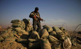 An Afghan security force member stands at the site of a car bomb explosion in Khogiani district of the eastern Nangarhar province, Afghanistan, Feb. 7, 2021.