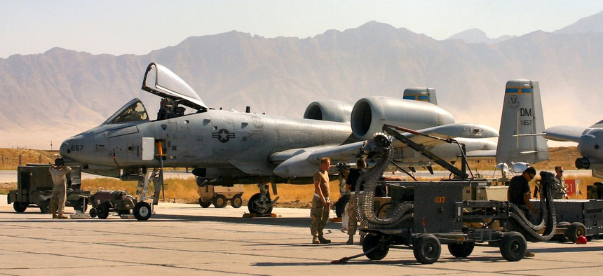 An A-10 Thunderbolt II takes off on a combat mission in Afghanistan as A-10 crew chiefs, weapons loaders, and an avionics specialist ready others for another mission.