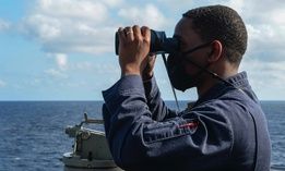 Ens. Ryan Simpson stands on the bridge wing of the guided-missile destroyer Russell while operating in the South China Sea last week.