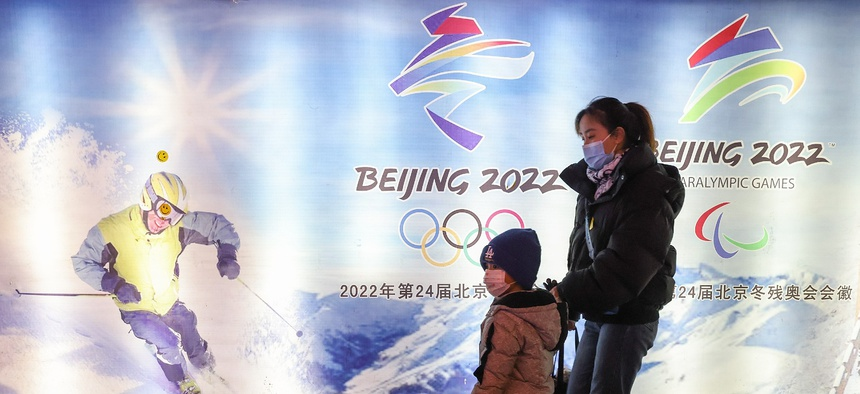 People wear protective masks as they walk front the logos of the 2022 Beijing Winter Olympics at Yanqing Ice Festival on February 26, 2021 in Beijing, China.
