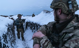 Ukrainian servicemen walk along a snow-covered trench guarding their position at the frontline near Vodiane, about 750 kilometers (468 miles) south-east of Kyiv, eastern Ukraine, Saturday, March 5, 2021.